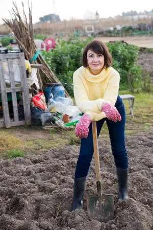 Female gardener standing with spade Foto de archivo