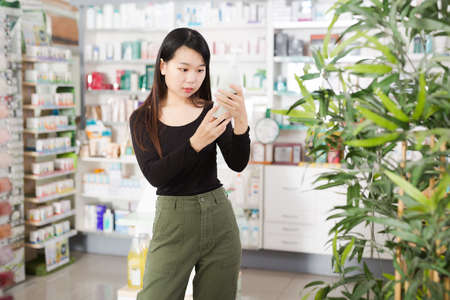 Young chinese woman chooses antibacterial at the pharmacy