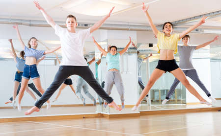 Group of young dancers jumping together in class