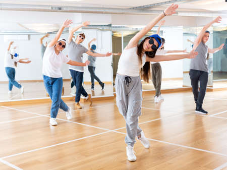 Joyous boy and girls dancing hip hop at lesson in the class