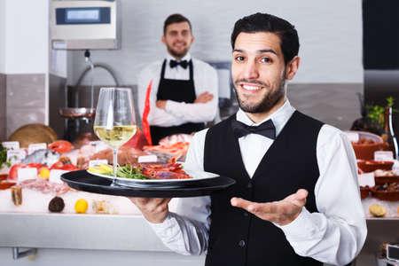 Waiter standing in fish restaurant