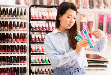 Young cheerful Asian woman holding nail polish samples in cosmetics store