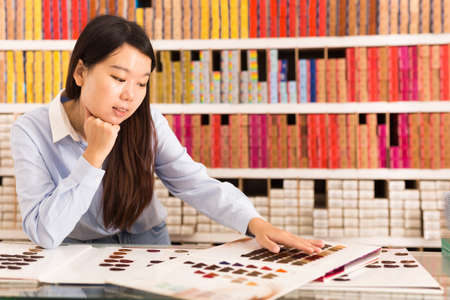 Female choosing hair dye from samples