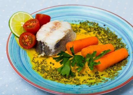 Hake prepared on steam and served with vegetable pate, carrots, lemon and tomatoes