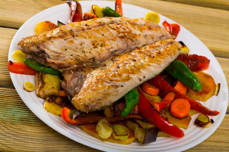 Baked spanish mackerel and different vegetables at plate, bulgarian cuisine