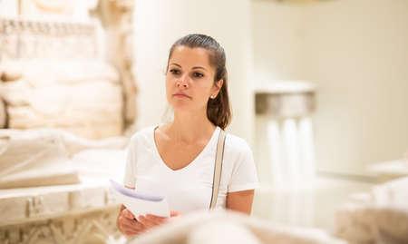 Woman observing sculptures exposition in art museum