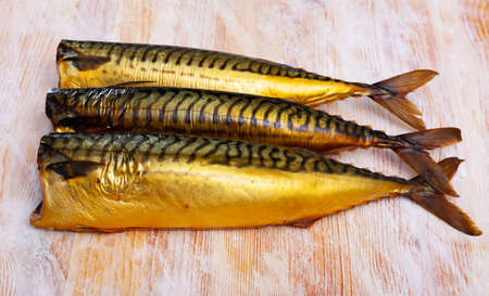 Cold-smoked mackerel without head on wooden table