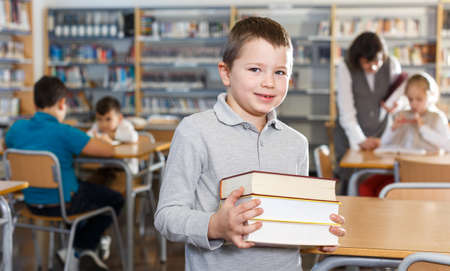 Smiling boy standing with pile of books