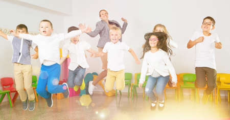Children with teacher jumping together in schoolroom 写真素材