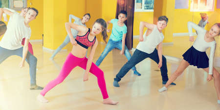 Tweens exercising with coach in choreography class