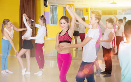 Children dancing rock-and-roll in pairs in choreography class wi