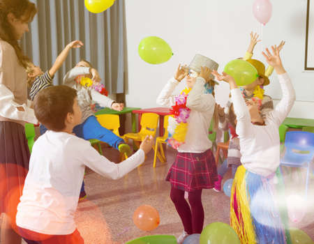 Kids and teacher playing with balloons