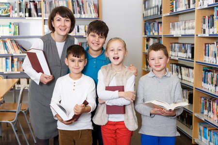 Female librarian with happy children near bookcase