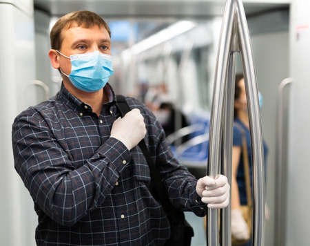 Man in disposable mask in subway train Imagens
