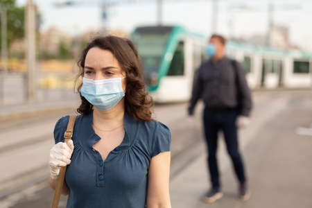 Woman in disposable mask at tram stop