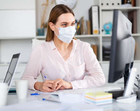 Businesswoman in protective equipment working on laptop in office