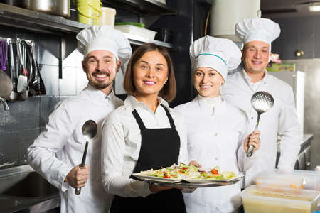 attentive woman waiter collecting dishes from restaurant kitchen