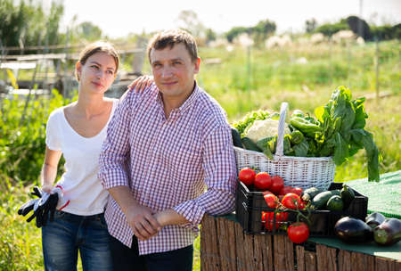 Young family couple with harvest of vegetables in garden outdoor