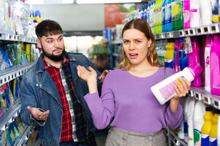 Couple shopping detergent at supermarket