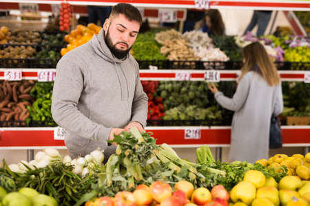Adult man is choosing leek and celery in the grocery store