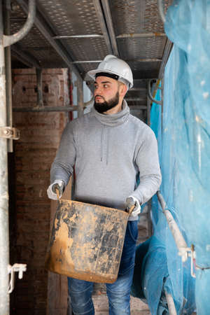 Contractor carrying bucket with cement mortar