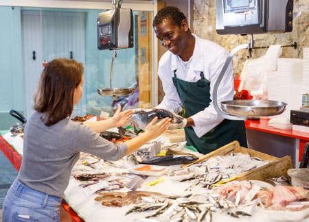 Salesman serving customer raw fish Stock Photo