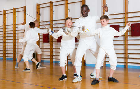 Fencing instructor with young fencers in training room Stock Photo