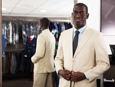 Portrait of male client choosing classic beige jacket in the mall
