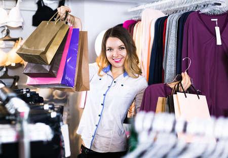 female shopper examining long sleeve shirts in underwear shop