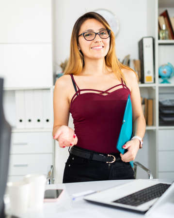 Woman manager in glasses holding clipboard in office