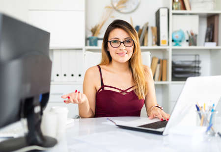 Young colombian woman in glasses working with laptop Zdjęcie Seryjne