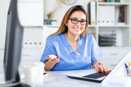 Doctor in uniform is working behind laptop in hospital