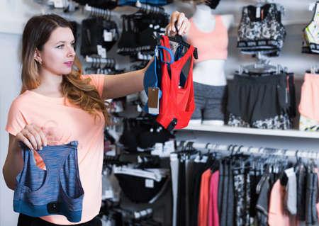 Smiling girl customer choosing sports lingerie Stockfoto