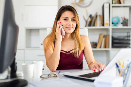 Woman using phone and working with laptop in office