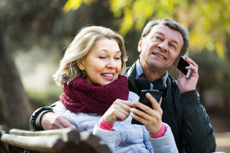 Mature couple with smartphones outdoors.