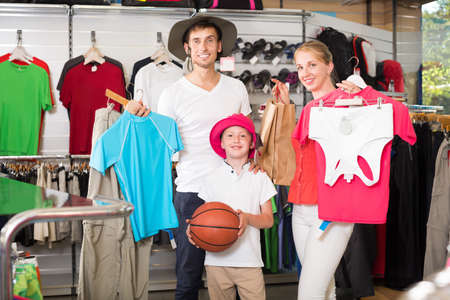 Young smiling parents with boy in sport store