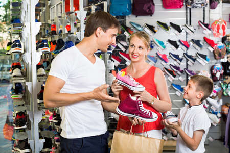 Cheerful young parents with boy in school age shopping shoes