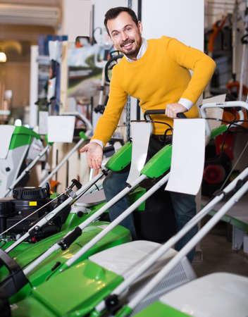 Salesman demonstrates petrol lawnmower Stockfoto