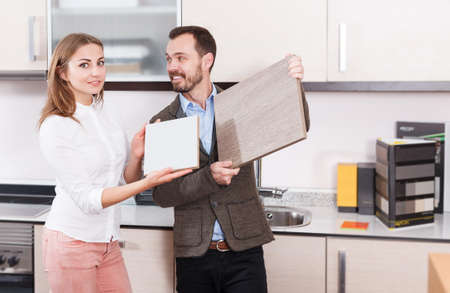Young man and woman choosing material for kitchen furniture