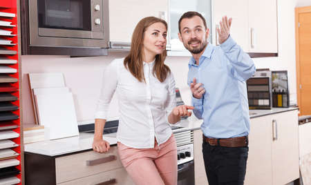 Woman with husband discussing in salon of kitchen furniture
