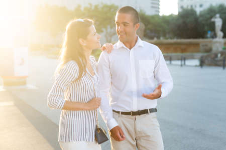 Young couple strolling through sunny city streets Stockfoto
