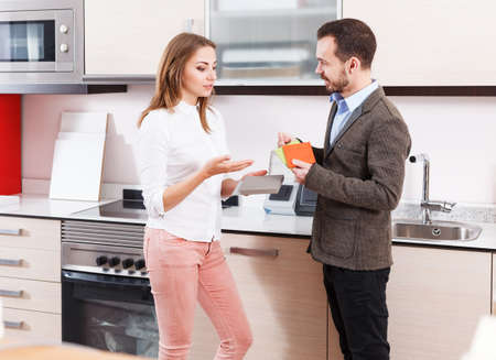 Couple choosing materials for kitchen furnishing
