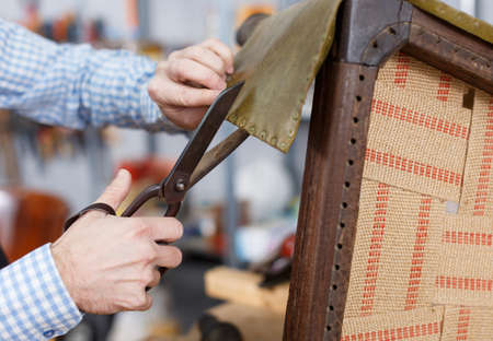 Man cutting leather upholstering chair