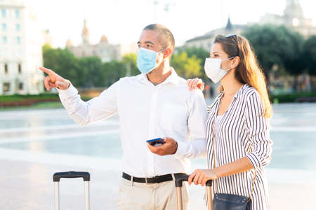 Couple of tourists in face masks admiring city views