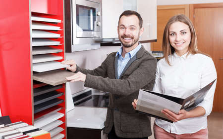 Young female seller consulting male in shop of kitchen furnishing Stok Fotoğraf