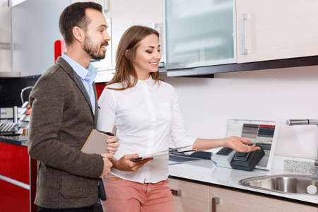 Polite salesgirl helping young man in choice of mixer tap in kitchen furniture salon