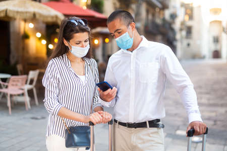 Couple of travelers in face masks reading about sights in smartphone