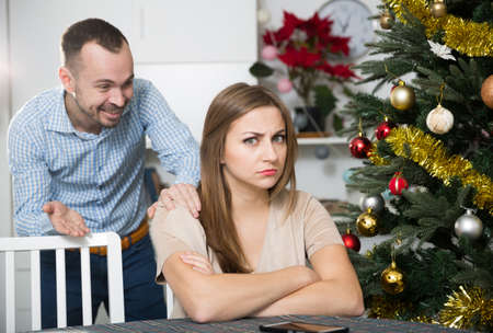 Man calming offended girl on Christmas Eve