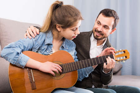 Male tutor assisting teenage pupil in learning how to play guitar
