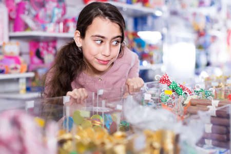 glad schoolgirl delighted with choosing lollipop in store
